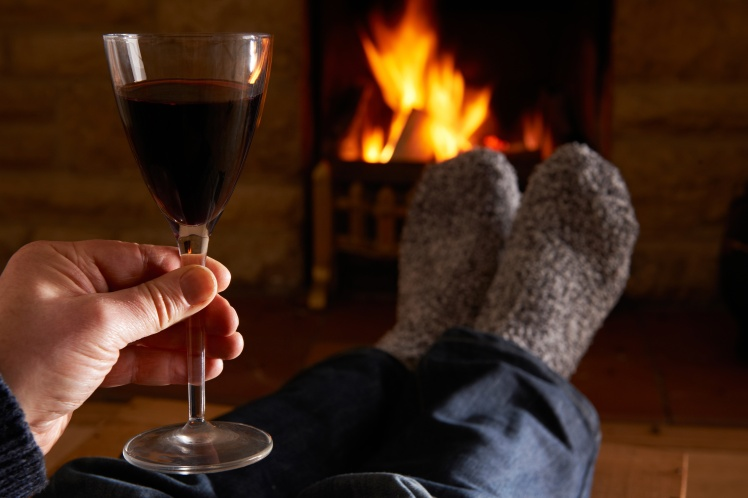 Man With Glass Of Red Wine Relaxing By Fire